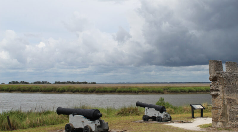 Two cannons pointing out at water